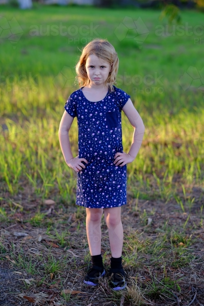 Girl with a frown and hands on hips - Australian Stock Image