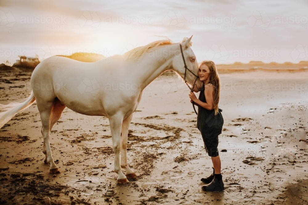 Girl with white horse on the beach at sunset - Australian Stock Image