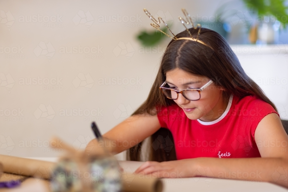 girl wrapping present at Christmas time with antler headband - Australian Stock Image