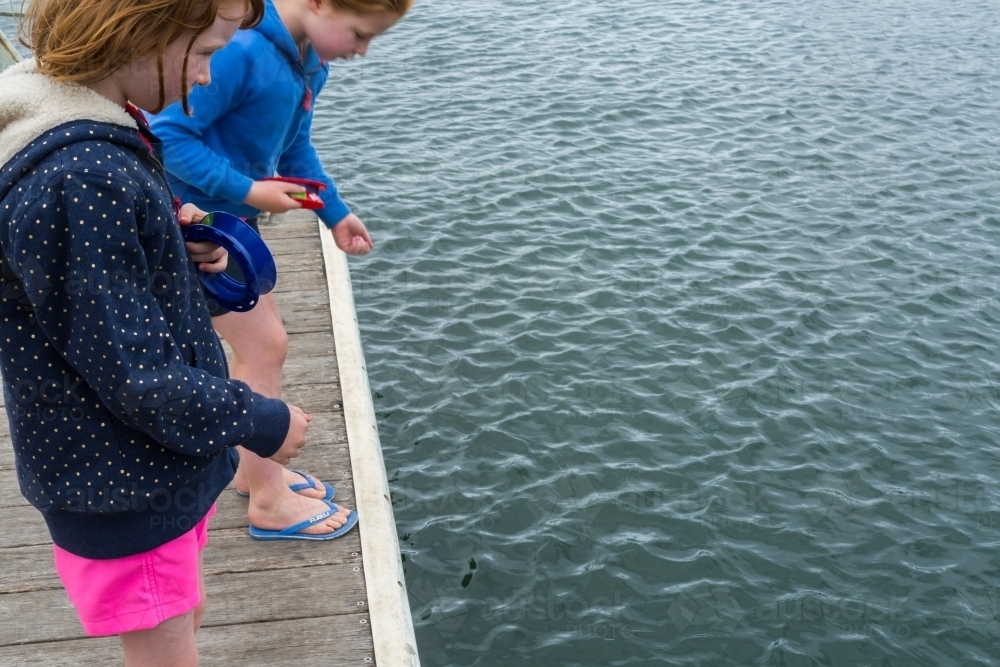 girls fishing with hand reels from a wooden jetty - Australian Stock Image