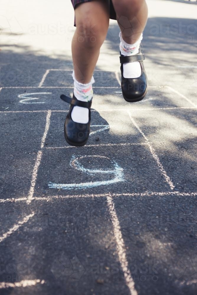Girls legs jumping on a hopscotch game - Australian Stock Image