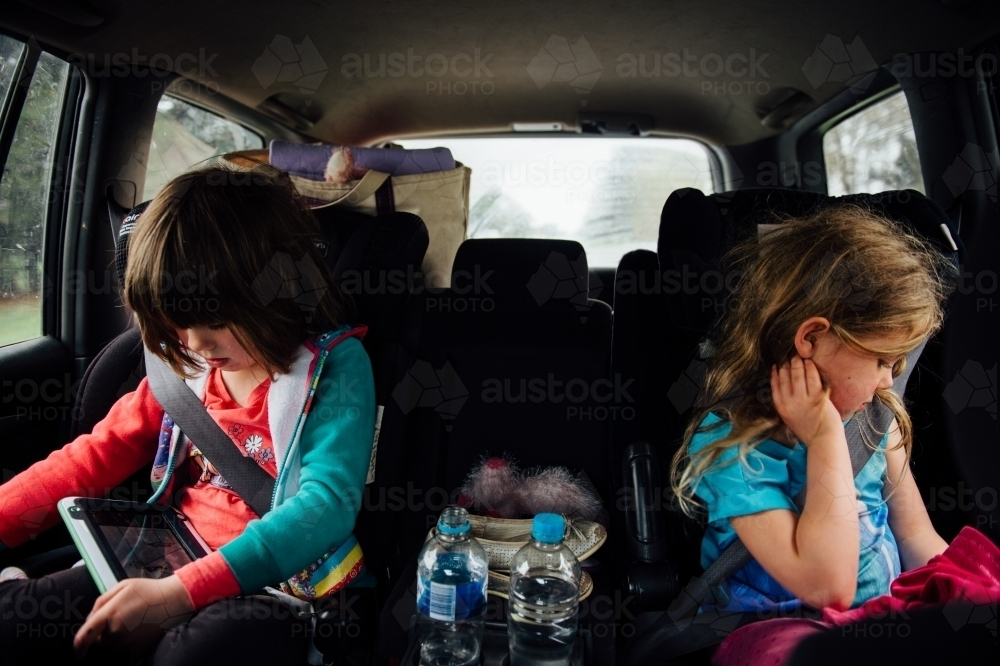 Girls sitting in backseat of car playing - Australian Stock Image