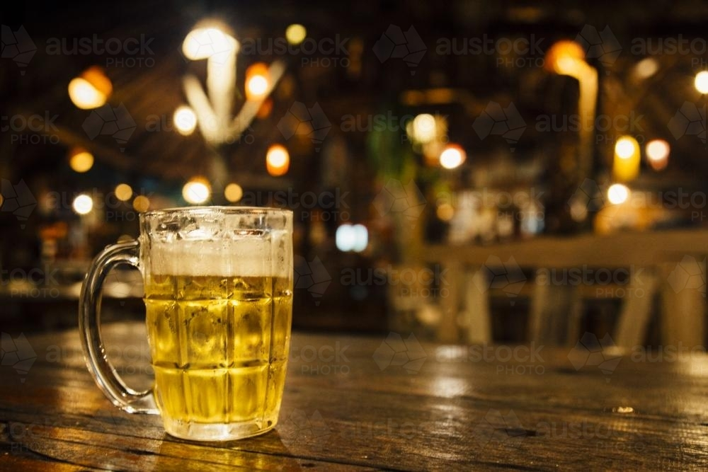 Glass of cold beer sitting on a table - Australian Stock Image