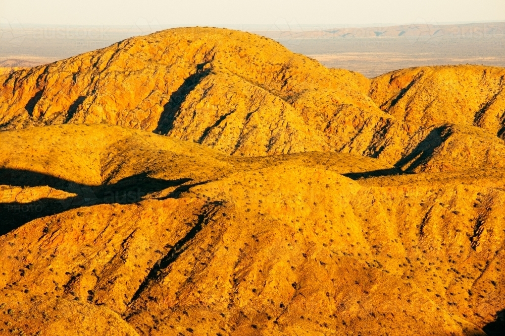 Golden light over the mountains of the Chewings Range in Central Australia. - Australian Stock Image