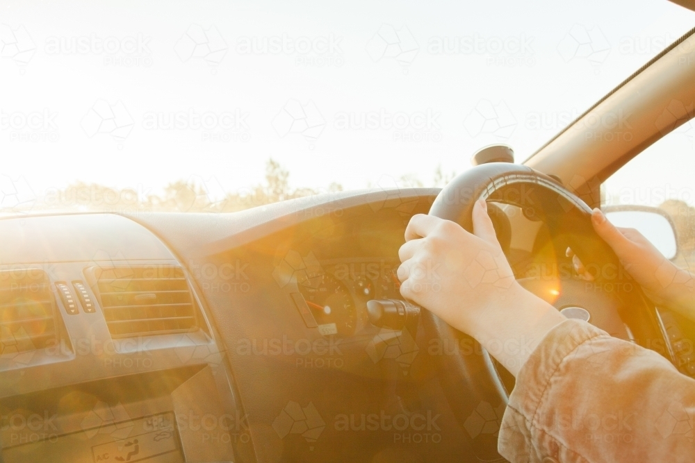 Golden sunlight flare over steering wheel and hands of car driver - Australian Stock Image