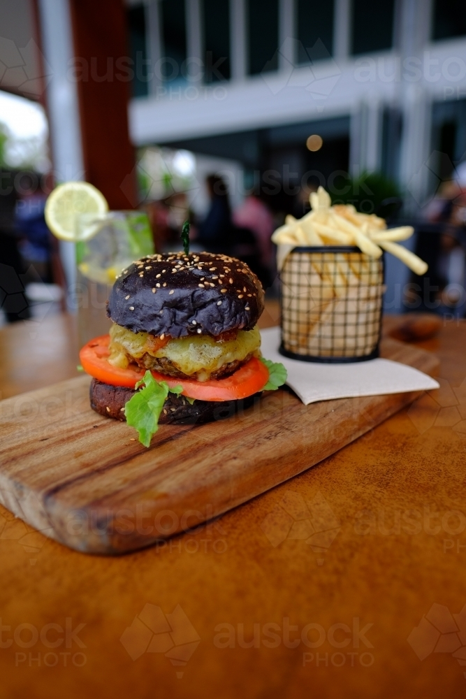 Gourmet burger in black brioche bun served with chips on a platter at a trendy cafe - Australian Stock Image