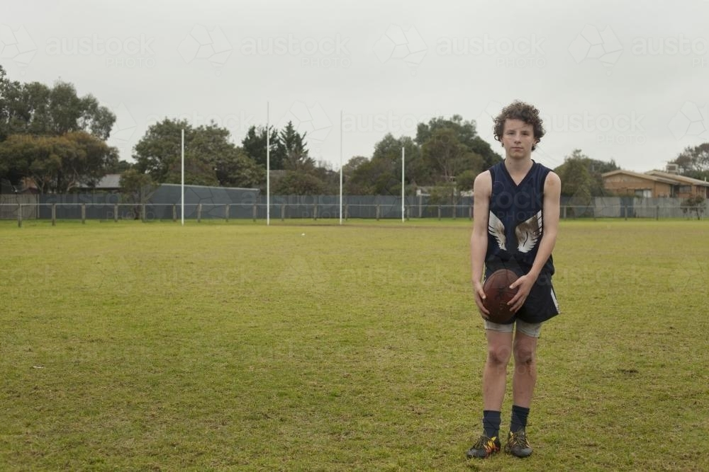 Grassroots Footy player standing with ball on local football ground - Australian Stock Image