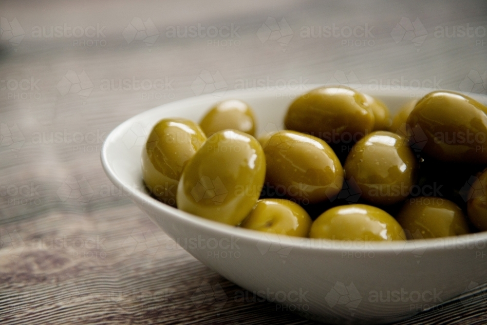 Green Olives In A Bowl on Wood - Australian Stock Image