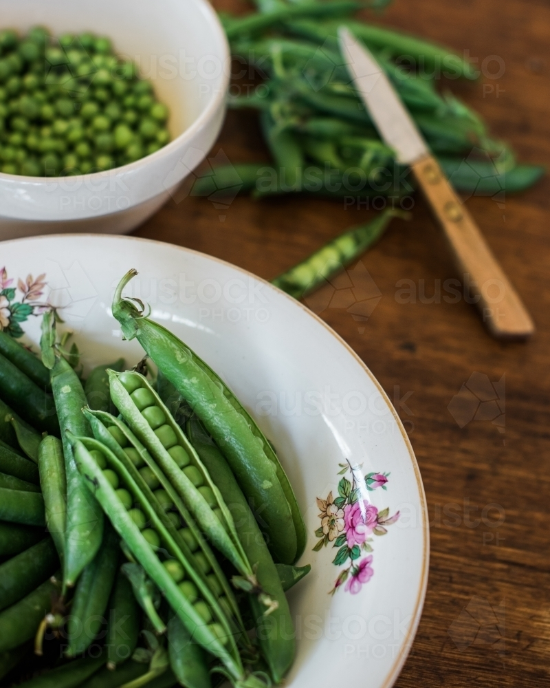 Green pea pods in bowl on table - Australian Stock Image