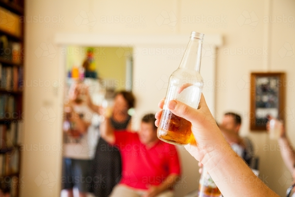 Hand holding up a bottle of beer for a toast at family gathering - Australian Stock Image