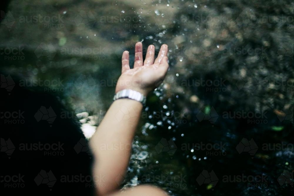 Hand playing with water - Australian Stock Image