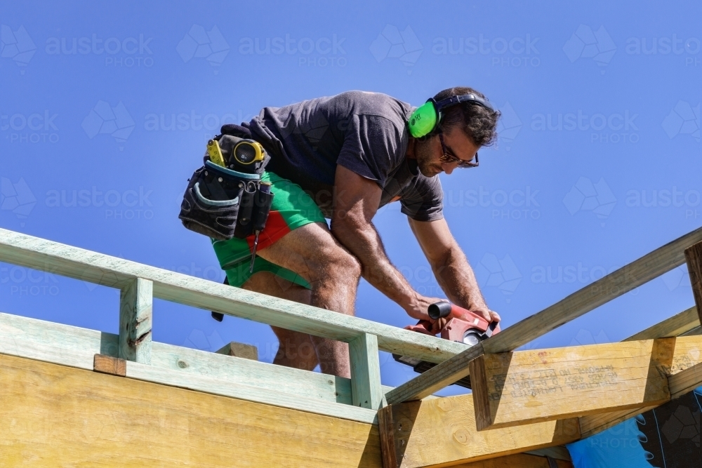 Image of Handsome young builder working with circular saw on timber ...
