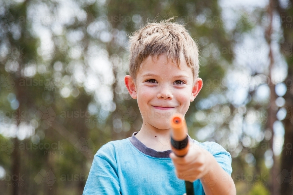 Happy boy looking at camera holding hose - Australian Stock Image