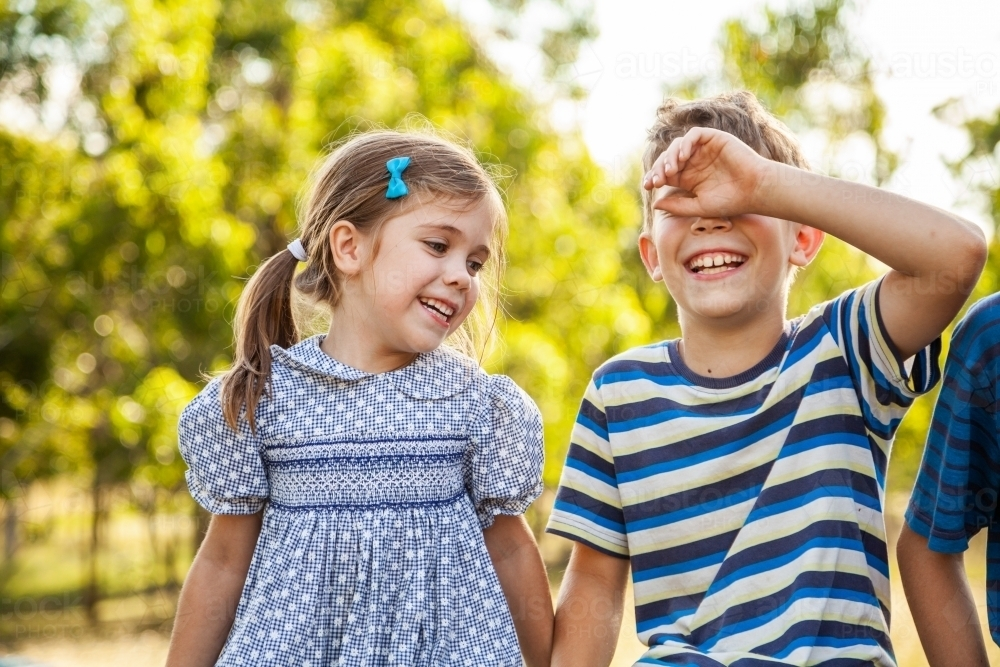 Happy brother and sister laughing together outside - Australian Stock Image
