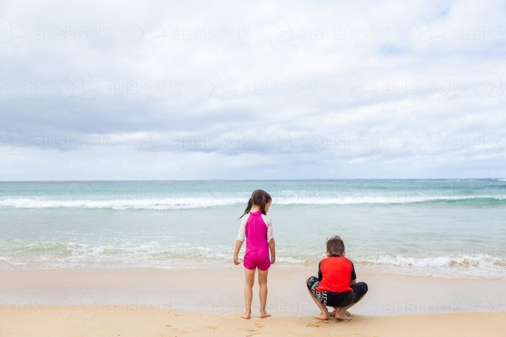 Happy brother and sister playing together on the beach - Australian Stock Image
