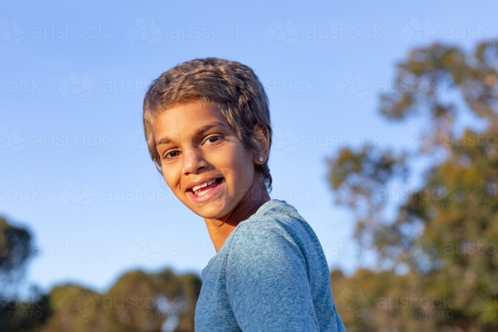 happy child looking over her shoulder at the camera - Australian Stock Image