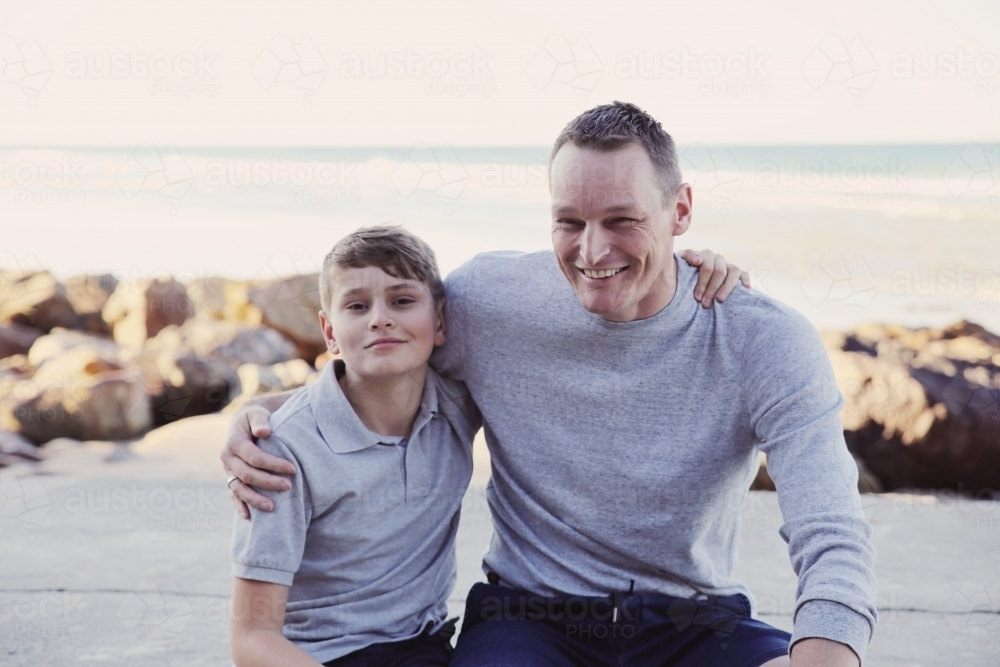 Happy father and teen son on the beach - Australian Stock Image