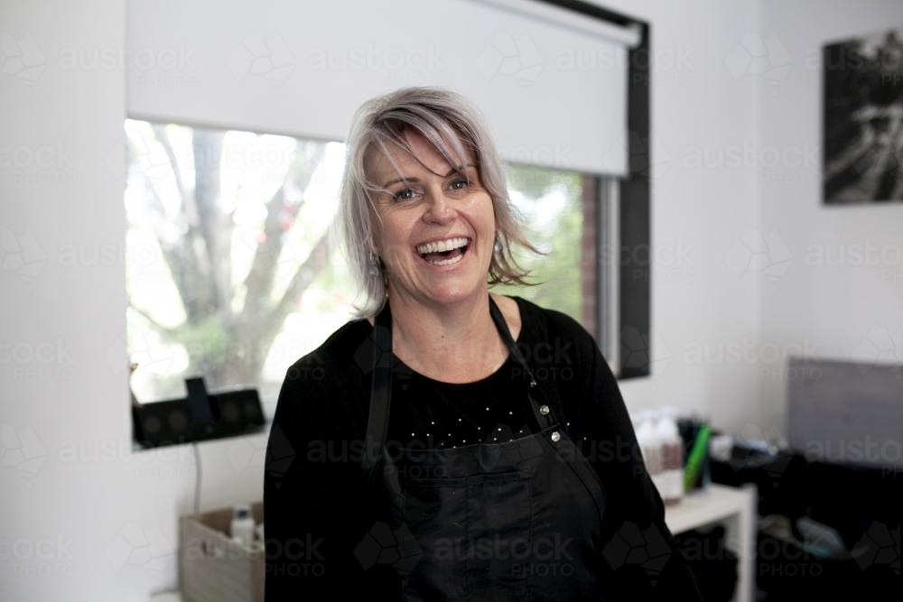 Happy female hairdresser laughing with salon in background - Australian Stock Image