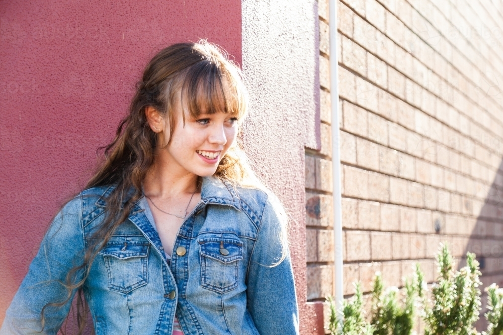 Happy female teenager wearing denim jacket in urban setting - Australian Stock Image