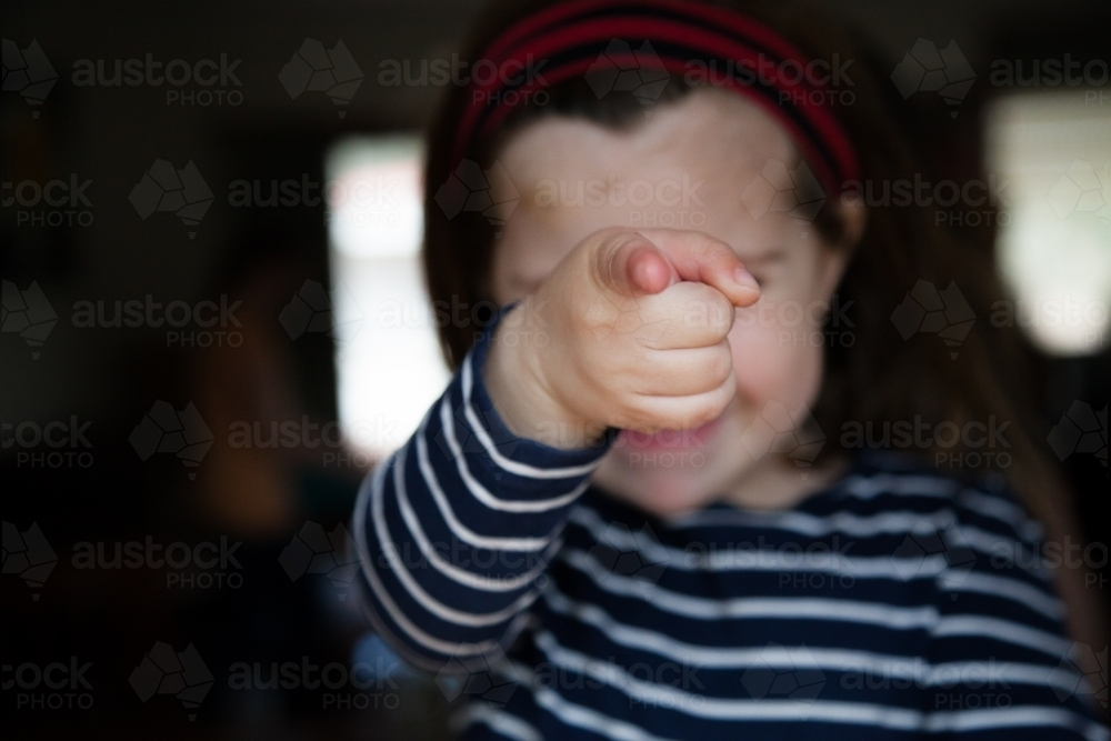 Happy little girl pointing at camera focus on finger - Australian Stock Image