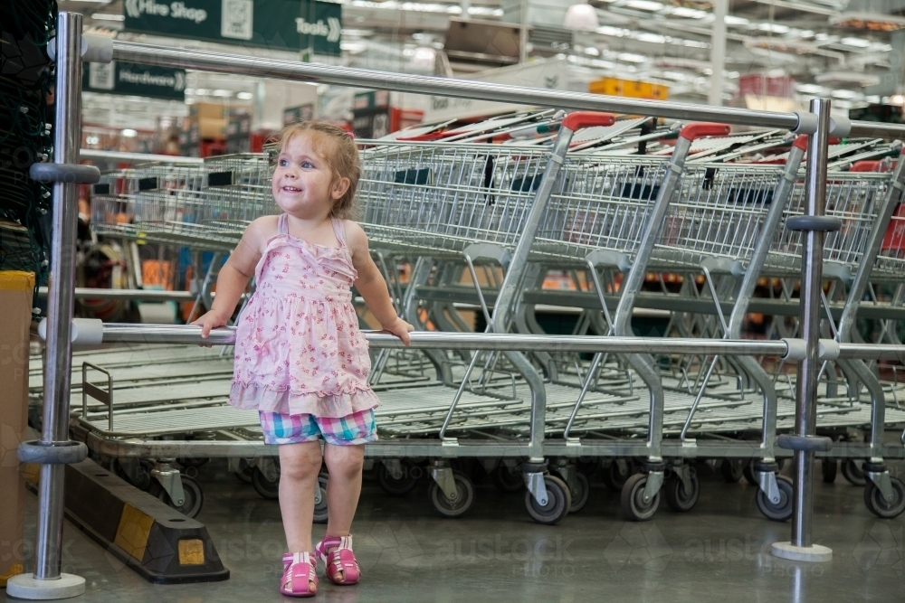 Happy little girl running around in the shops - Australian Stock Image
