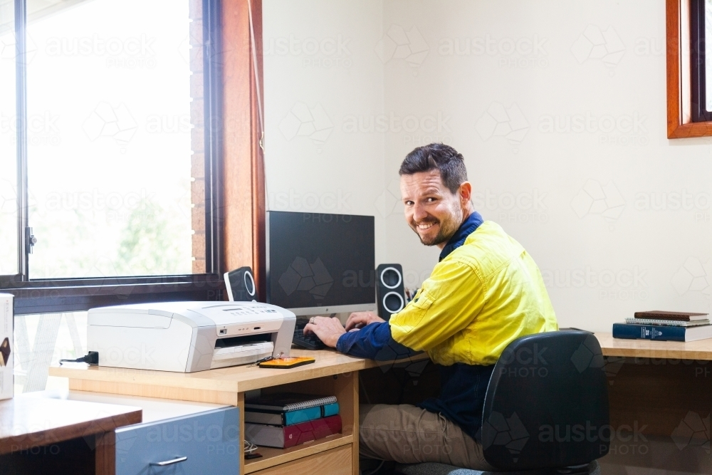 Happy male tradie at computer in home office - Australian Stock Image