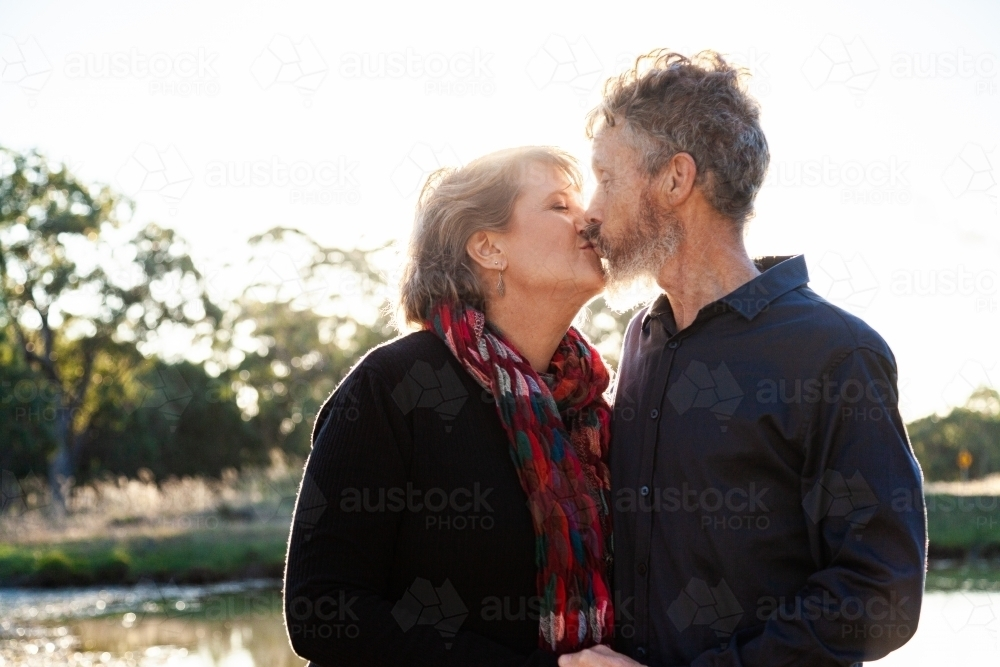 Happy middle aged couple kiss beside dam on farm - Australian Stock Image