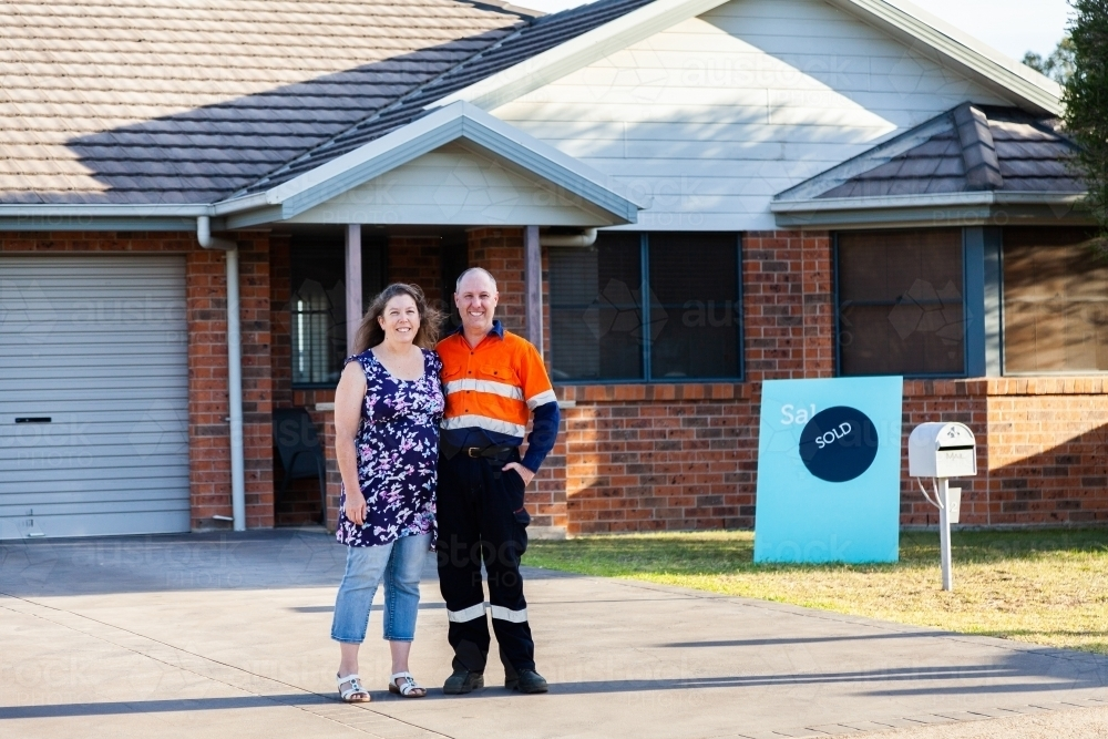 Happy middle aged couple smiling with newly purchased house sold sign - Australian Stock Image