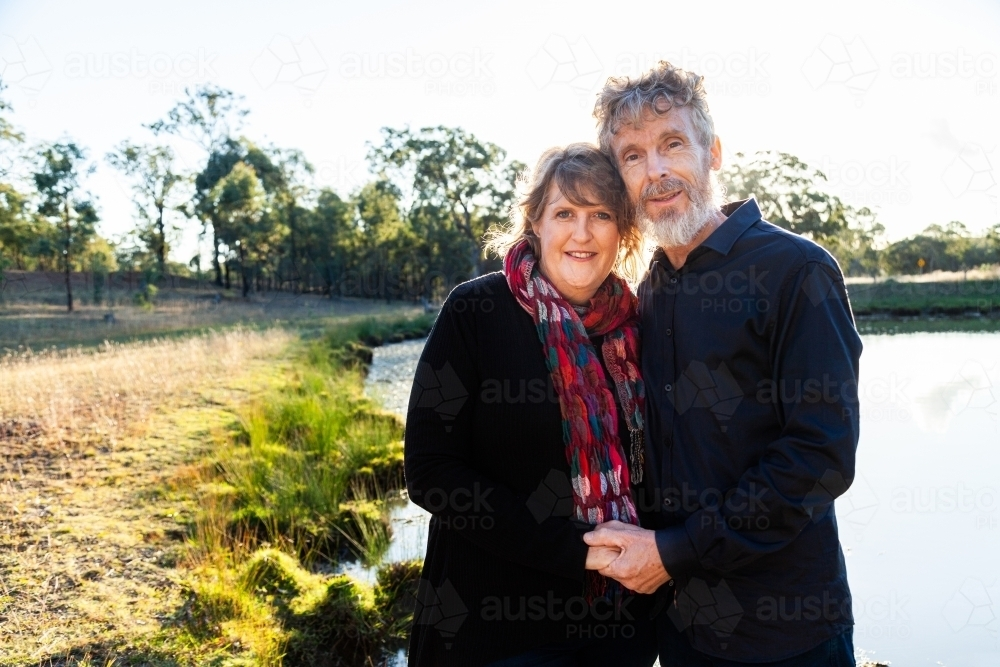 Happy middle aged couple together on farm beside dam - Australian Stock Image