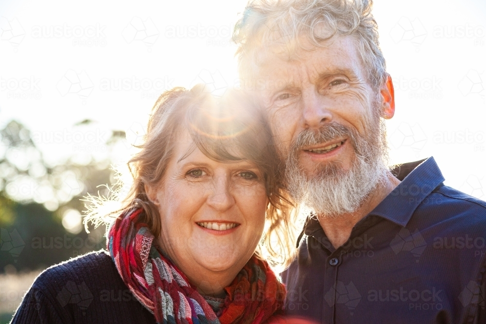 Happy middle aged couple together with sun flare close up - Australian Stock Image