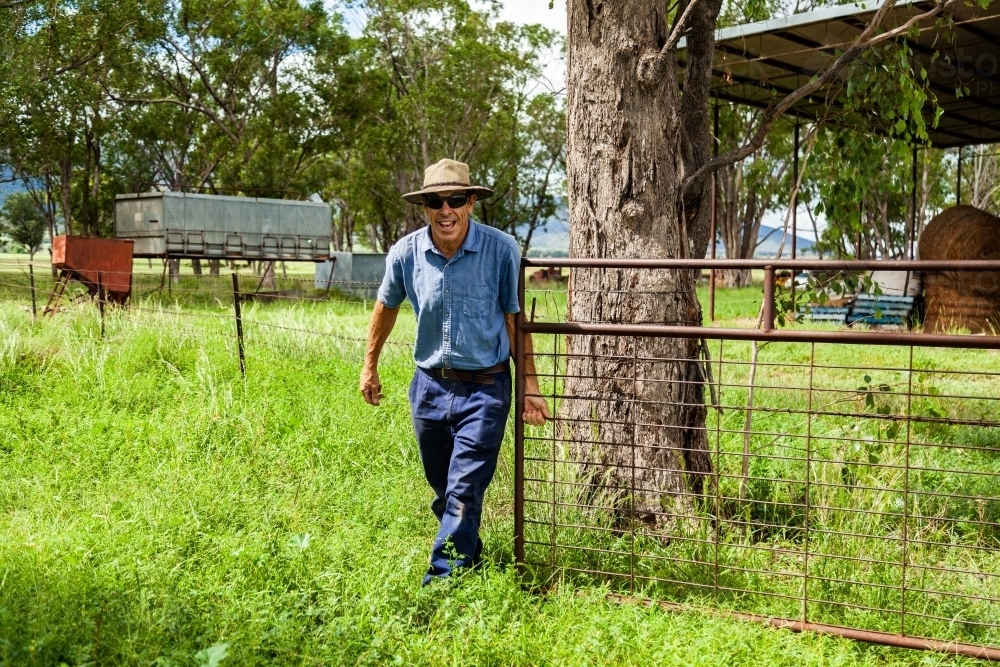 Happy middle aged farmer opening gate to paddock - Australian Stock Image
