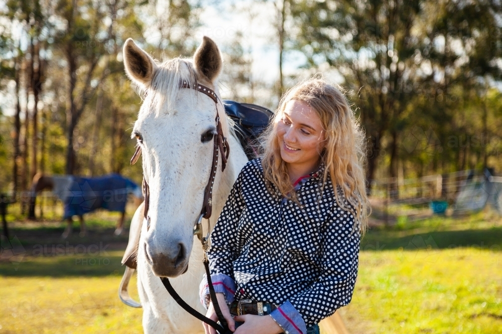 happy person leading her horse through paddock - Australian Stock Image