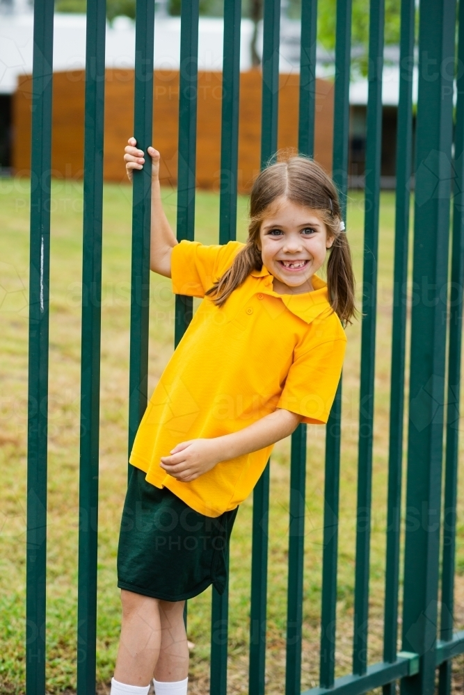 Happy school girl swinging off the school fence - Australian Stock Image