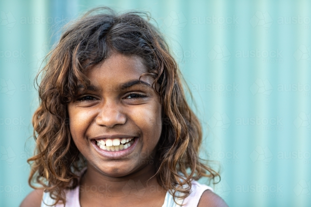 happy smiling 8 year old girl looking at camera - Australian Stock Image