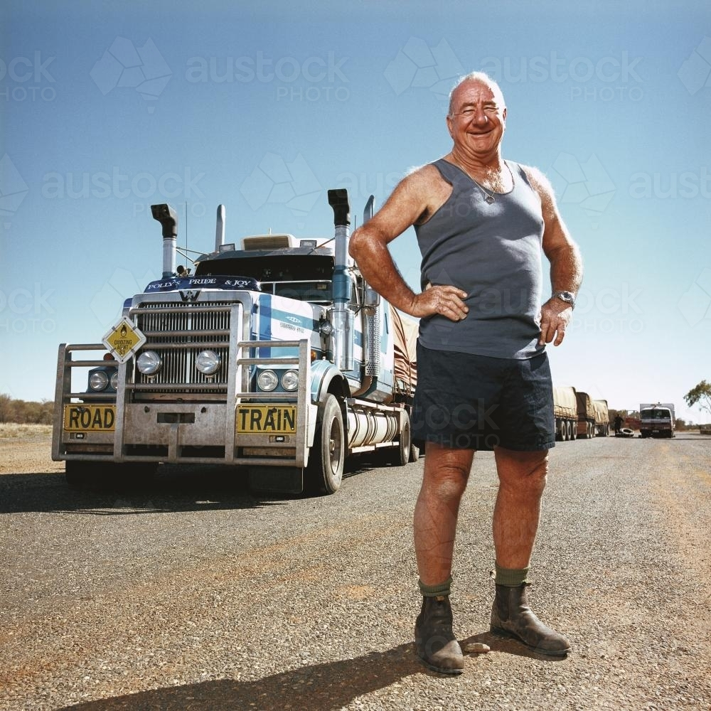 Happy truck driver standing front of road train - Australian Stock Image