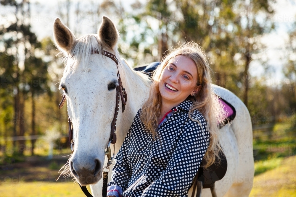 Happy young adult person laughing with her horse in Aussie sunlight - Australian Stock Image