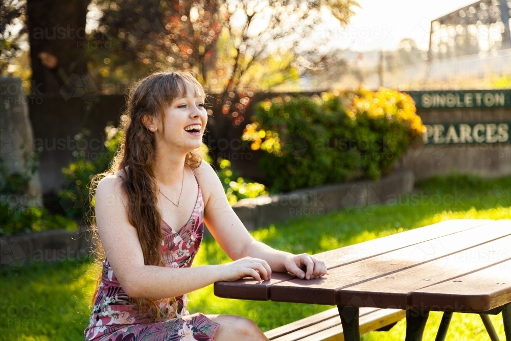 Happy young adult sitting at park bench in autumn - Australian Stock Image