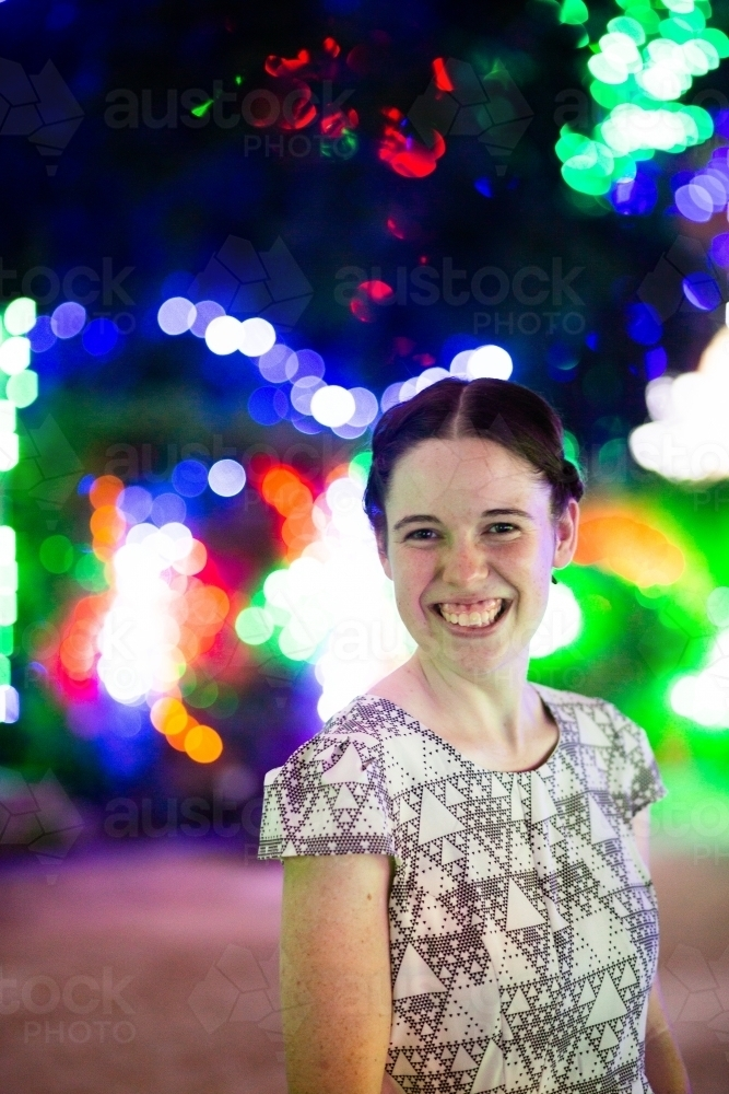 Happy young adult woman smiling during Christmas season with bokeh lights - Australian Stock Image