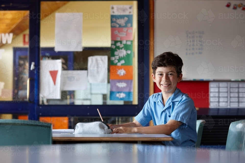 Happy young school boy writing in classroom - Australian Stock Image
