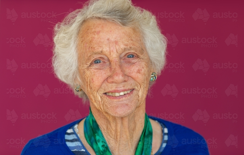 head and shoulders of elderly lady with grey hair looking at camera - Australian Stock Image