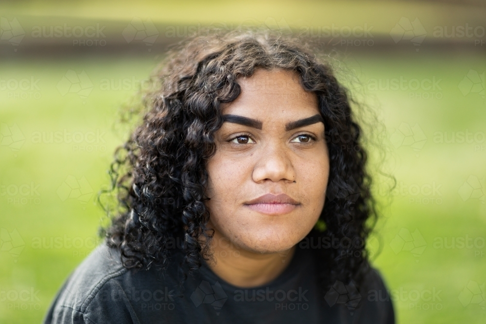 head and shoulders of indigenous girl with curly hair and blurry background - Australian Stock Image