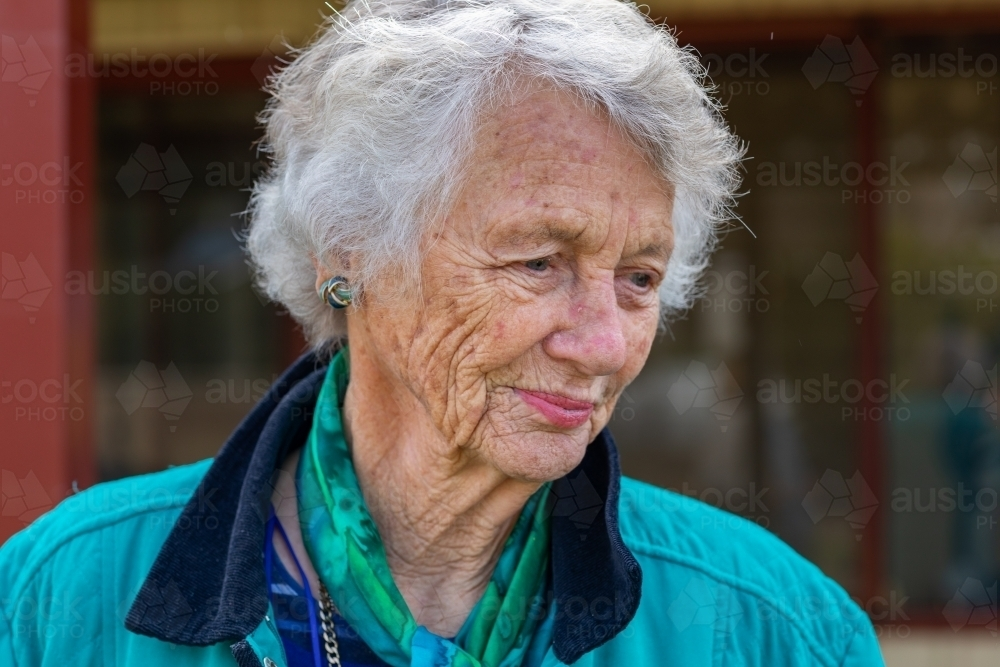 head and shoulders of old lady with grey hair and wrinkled skin looking away - Australian Stock Image