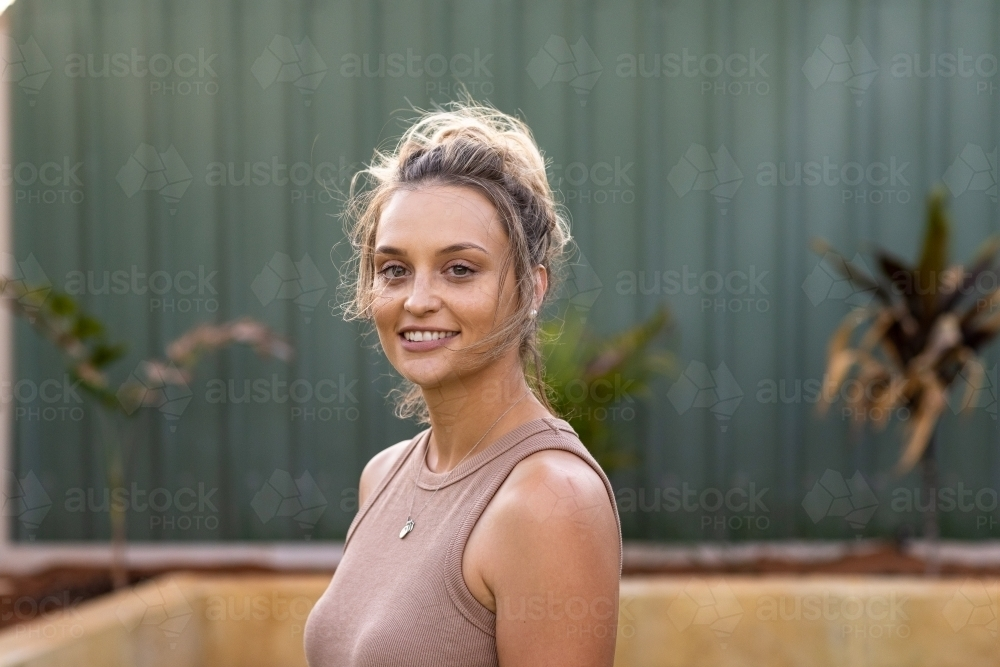 head and shoulders of tanned young woman looking at camera - Australian Stock Image