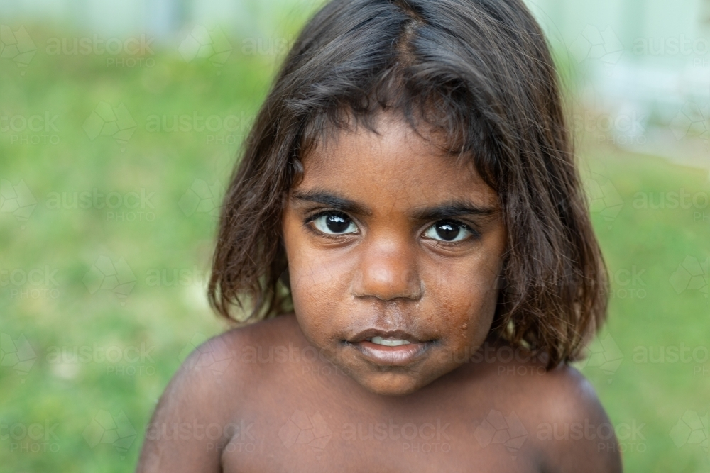 head and shoulders of young child looking up at the camera - Australian Stock Image