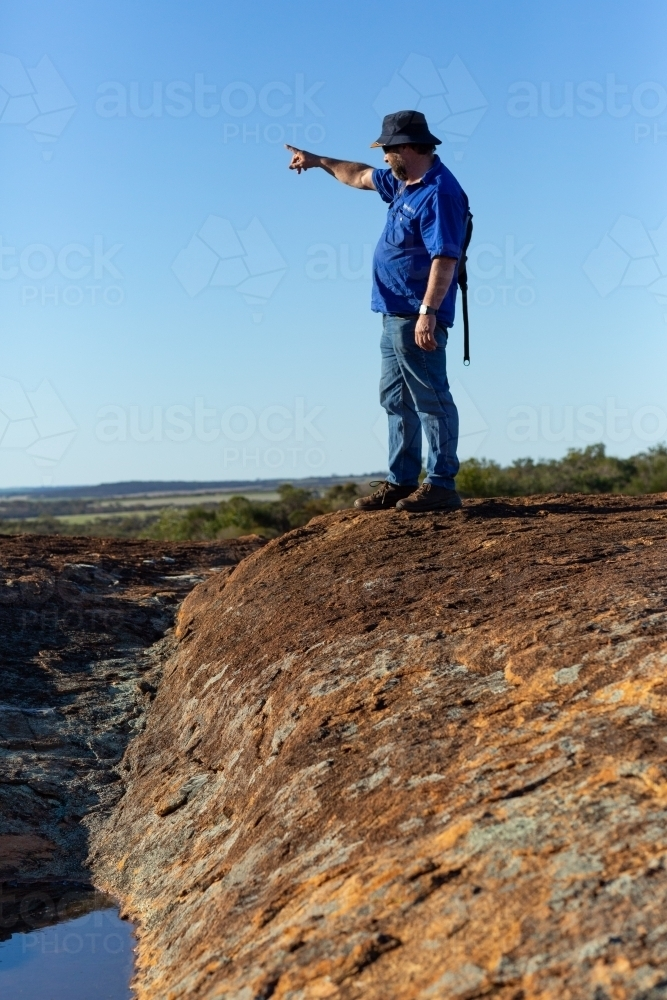 hiker on a rock pointing into the distance against a blue sky - Australian Stock Image