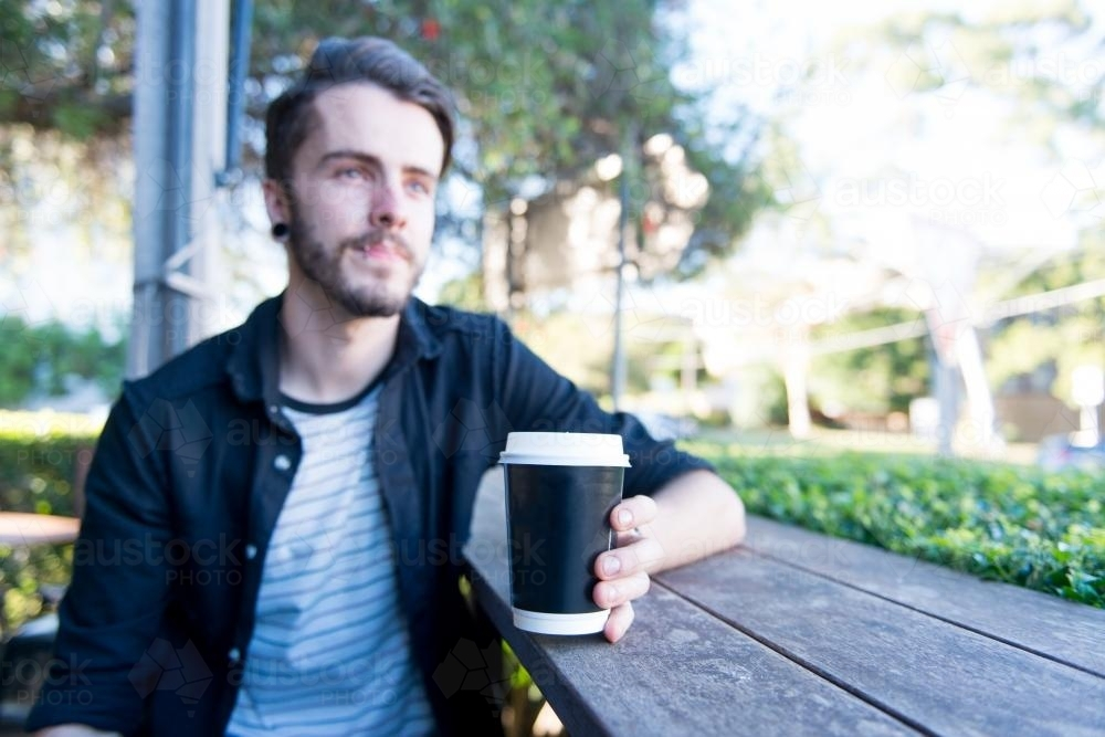 Hipster man sitting outdoors with a take away coffee - Australian Stock Image