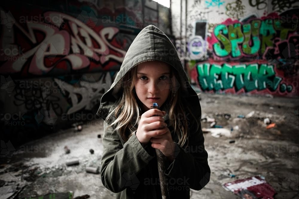 Hooded girl holding a pipe with attitude - Australian Stock Image