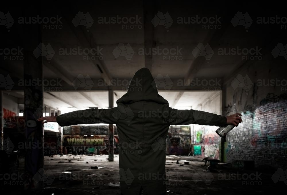 Image of Hooded girl holding spray paint in a pose of