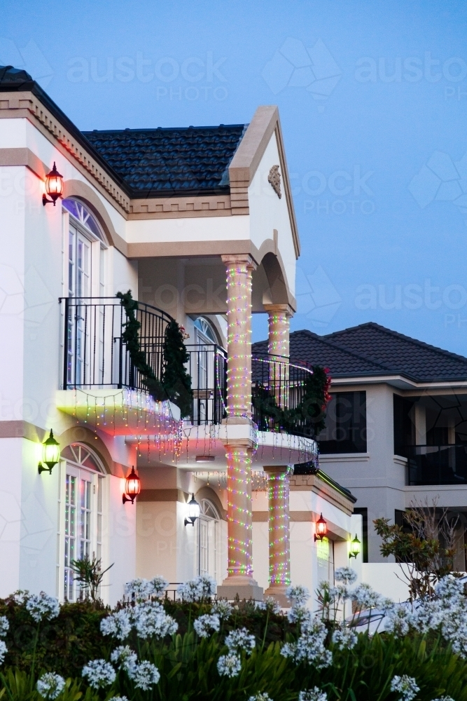House on street corner at dusk with Christmas lights and decorations - Australian Stock Image