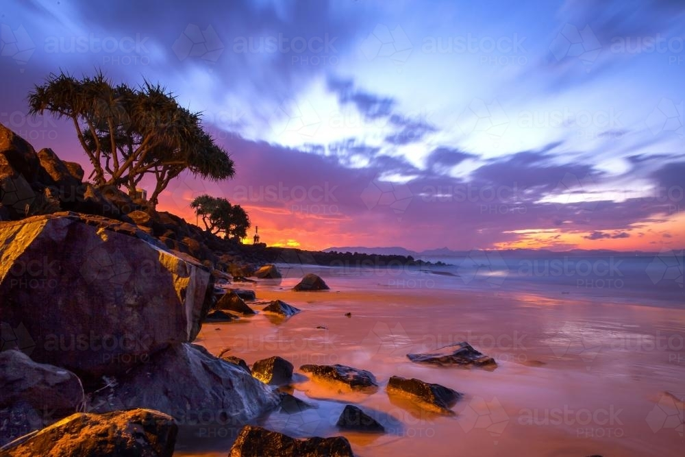 Incredible colourful sunset at Byron Bay over the water - Australian Stock Image